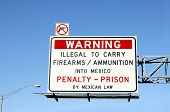 Warning sign above road urging travelers not to carry firearms and ammunition across to border from the U.S. to Mexico