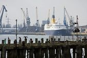 The derelict old pier at Southampton docks with cruise ship, dockside and cranes behind.