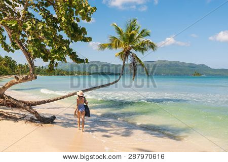 poster of Traveler Girl Walking In Bikini On A Tropical Beach. Young Girl Traveler Walking In Nature. Traveler