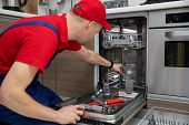 Home Appliance Maintenance - Repairman Repairing Dishwasher In Kitchen poster