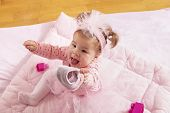 High Angle View Of Baby Girl Wearing Pink Tutu Skirt, Sitting On A Duvet And Holding Her Shoe, Playi poster