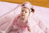 High Angle View Of A Beautiful Baby Girl Wearing Pink Tutu Skirt Sitting On A Pink Duvet, Looking Up poster