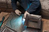 Blacksmith Soldering Metal Plates To A Metal Stand With Ornament. The Blacksmith In White Blacksmith poster