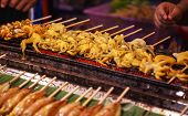 Traditional Asian Thai Street Food And Fast Food, Delicious Grilled Squid Calamari Skewers In Food M poster