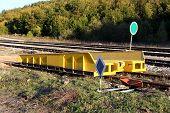 Yellow Strong Metal Railway Loading Ramp Mounted On Railway Tracks Next To Railway Switch Mechanism  poster