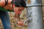 stock photo of spqr  - Italian girl drinking water from a fountain in Rome in a hot summer day - JPG