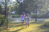 Child Playing With Garden Sprinkler. Kids Run And Jump. Summer Outdoor Water Fun In The Backyard. Ch poster