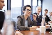 Portrait Of Smiling Businesswoman Speaking To Microphone During Press Conference Or Training Seminar poster