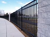 Tall Curving Black Fence By A Sidewalk
