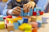 A Child Plays With Colored Wooden Blocks At Home.kid Plays And Builds Buildings And Towers With Wood poster