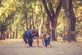 Little Boy And His Father Exercising Together In The Park. Father And Son Spend Time Together And Le poster