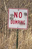 No Dumping Sign With Gun Shot Holes