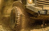 Off-road Vehicle Goes On Mountain Way. Bottom View To Big Offroad Car Wheel On Country Road And Moun poster