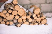 Firewood Under The Snow. Firewood In Winter. Waste From The Tree. Sawwood Tree. Woodpile Logs Lie Un poster
