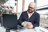 Successful Businessman Keep Working During Coffee Break. Young Bald Man In Casual Using Tablet And L poster