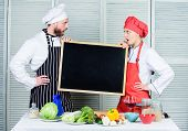 Gaining A Range Of Skills. Couple Of Man And Woman Holding Empty Blackboard In Cooking School. Maste poster