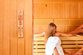 Wellness - young happy women in sauna of a Spa; focus is on a sand hour glass measuring time spent i