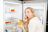 image of emaciated  - The woman greedy eats meal against an open refrigerator - JPG