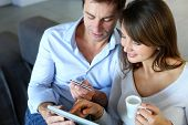 picture of 35 to 40 year olds  - Mature couple at home using credit card to shop online - JPG