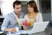 stock photo of 35 to 40 year olds  - Couple choosing paint colour for their new home - JPG