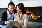 Couple sitting by fireplace and websurfing with tablet