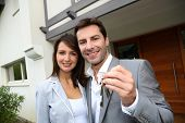 image of 35 to 40 year olds  - Couple in front of new home holding door keys - JPG