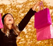 Photo of attractive woman expressing joy of her new purchase, happy good looking girl with pink shop