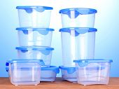 picture of tupperware  - Plastic containers for food on wooden table on blue background - JPG