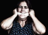 Portrait of a woman covering her mouth with a handkerchief to avoid talking isolated on black (useful to illustrate gender violence or discrimination)