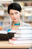 Woman surrounded with piles of books reads sitting at the table at the reading hall. Learning proces