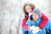 Happy winter travel couple. Man giving woman piggyback ride on winter vacation in snowy forest. Youn