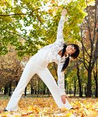 Pretty woman doing yoga exercises in the autumn park