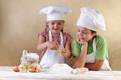 stock photo of apron  - Kids with chef hats preparing the cake dough  - JPG