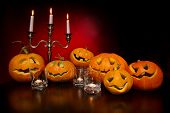 Halloween pumpkins with candelabra on a wooden desk over red background