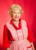 Sweet senior lady in her vintage apron.  Perfect retro grandmother or homemaker.  Red background.