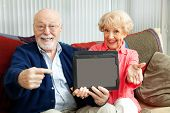 Senior couple pointing to a message on their tablet PC.