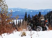 stock photo of camoflage  - Couple hunting in a nondiscript atv in the cold north - JPG