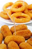 closeup of some plates with spanish croquettes and calamares a la romana, breaded and fried rings of