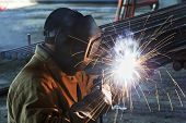 stock photo of manufacturing  - welder worker welding metal by electrode with bright electric arc and sparks during manufacture of metal equipment - JPG