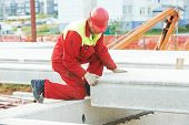 builder worker in safety protective equipment installing concrete floor slab panel at building const