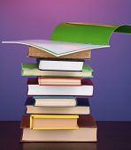 Stack of interesting books and magazines on wooden table on purple background