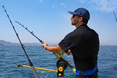stock photo of troll  - blue sea fisherman in trolling boat in action with downrigger and rod - JPG