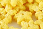Close up of yellow corn flakes as asterisks for healthy breakfast.