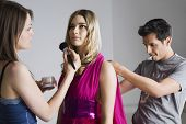 Designer and makeup artist preparing female model for photo shoot