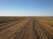 Country view of a long and straight dirt road leading into the distant horizon