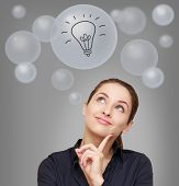 Thinking Smiling Woman Looking Up On Many Bubbles With Idea Bulb Sign