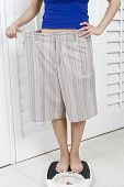 Lowsection of a woman in oversized shorts on bathroom scale