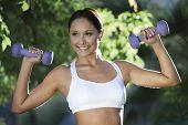 Lächelnde junge Frau trainieren mit Hanteln im park