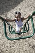Elevated view of a smiling young girl climbing jungle gym