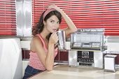 Beautiful young woman drinking shake in a diner